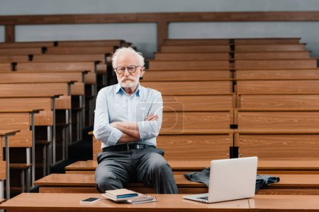 grey hair professor sitting in empty lecture room with crossed arms