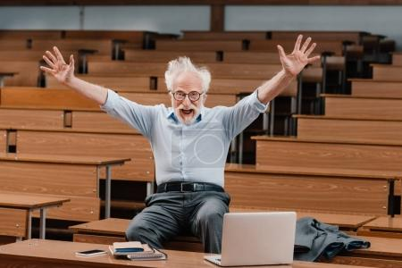 senior lecturer in empty lecture room screaming with hands up