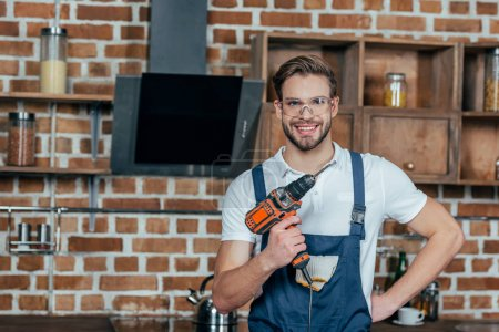 handsome young man holding electric drill and smiling at camera