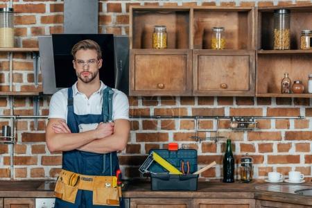 Foto de Reparador profesional joven guapo con correa de pie con los brazos cruzados y mirando a cámara - Imagen libre de derechos