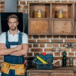 handsome young professional repairman with tool belt standing with crossed arms and looking at camera
