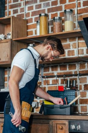 young repairman with toolbox working in kitchen