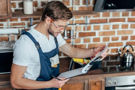 handsome young foreman in protective workwear writing on clipboard
