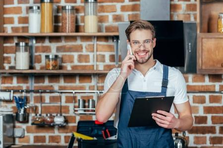 young repairman with clipboard talking by smartphone and smiling at camera in kitchen