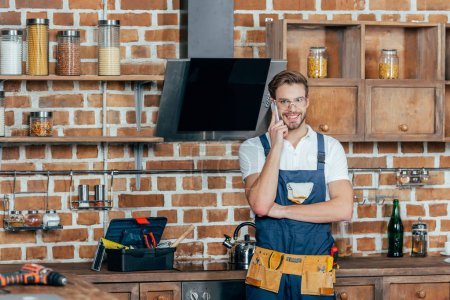handsome young repairman talking by smartphone and smiling at camera in kitchen