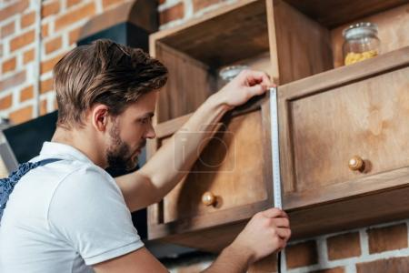 handsome young foreman measuring kitchen furniture with tape