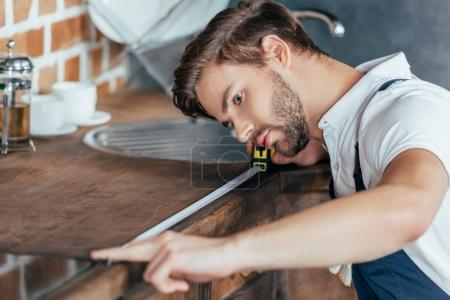professional young handyman measuring kitchen furniture with tape