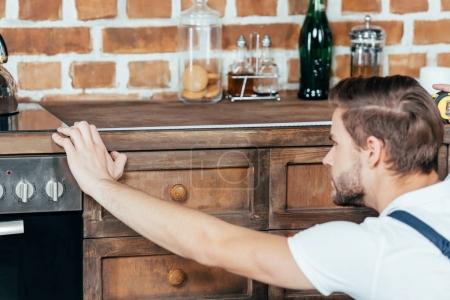 selective focus of young foreman measuring kitchen furniture with tape