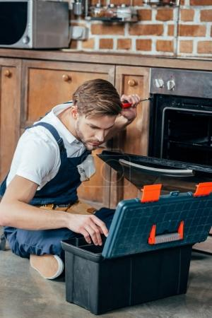 repairman looking at toolbox while fixing oven with screwdriver