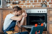 young repairman in protective workwear fixing oven in kitchen