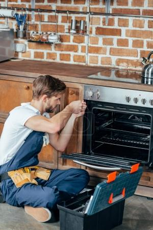 high angle view of young repairman fixing oven in kitchen