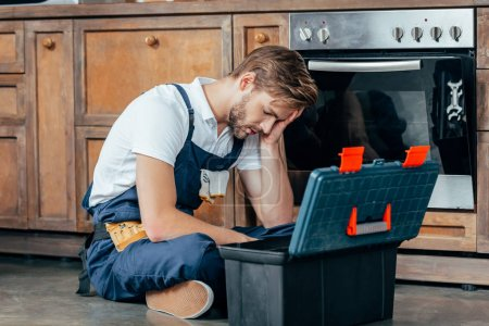 tired young foreman sitting with toolbox near broken oven