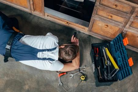 Photo for Top view of young repairman checking broken oven with flashlight - Royalty Free Image