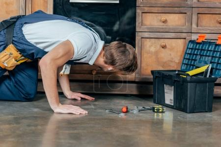 side view of young repairman with toolbox checking broken oven