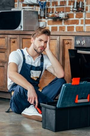 upset young foreman sitting with toolbox near broken oven