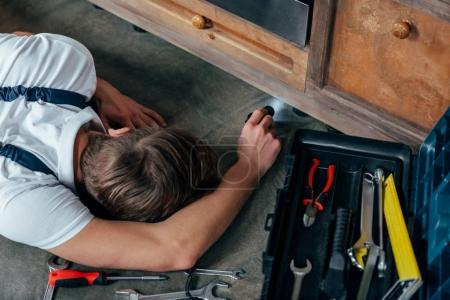 high angle view of young repairman checking oven with flashlight