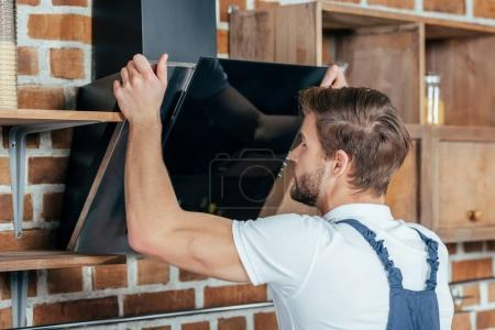 close-up view of handsome young handyman fixing extractor hood