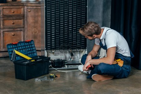 young handyman with toolbox sitting on floor and looking at broken refrigerator
