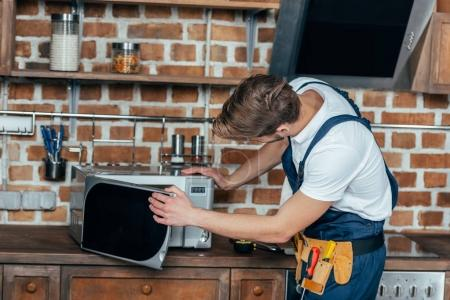 professional young foreman repairing microwave oven in kitchen