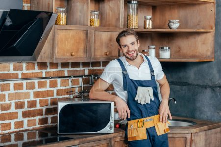 handsome young handyman leaning at microwave oven and smiling at camera