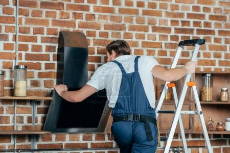 young master in protective workwear standing on ladder and repairing kitchen hood