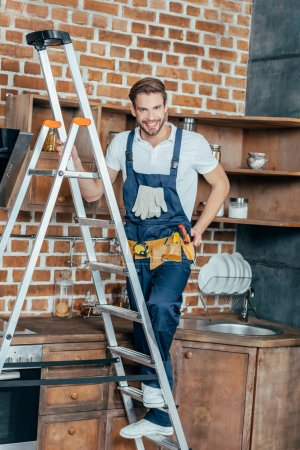 handsome young repairman standing on ladder and smiling at camera in kitchen