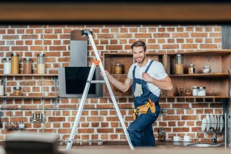 Photo pour Mise au point sélective du jeune contremaître permanent sur échelle et souriant à la caméra tout en fixant la hotte de cuisine - image libre de droit