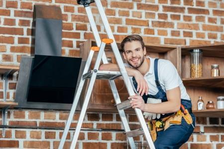Photo pour Beau chef d'atelier jeune debout sur une échelle et souriant à la caméra tout en fixant la hotte de cuisine - image libre de droit