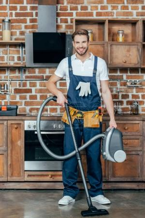 handsome young handyman holding vacuum cleaner and smiling at camera