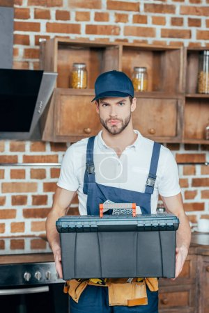 serious young home master holding toolbox and looking at camera