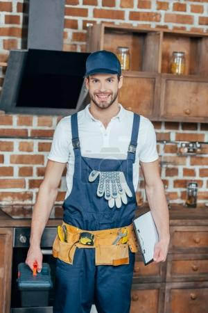 professional home master with toolbox and clipboard smiling at camera