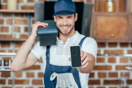 smiling young home master holding smartphone with blank screen
