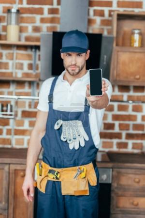 handsome young professional home master showing smartphone with blank screen
