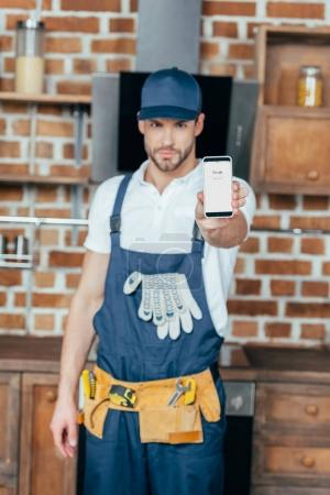 handsome young professional home master showing smartphone with google website