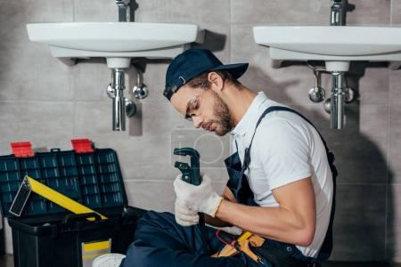 young professional plumber fixing sink in bathroom