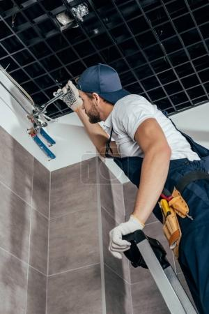 low angle view of plumber standing on ladder and working with pipes in bathroom