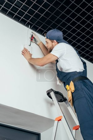 low angle view of young electrician standing on ladder and fixing home alarm