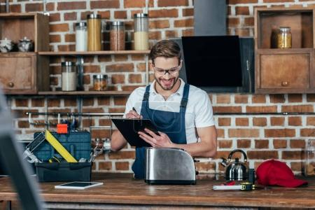 smiling young repairman writing on clipboard while fixing toaster