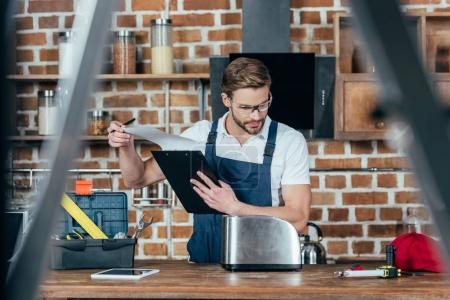 selective focus of young handyman holding clipboard and fixing toaster