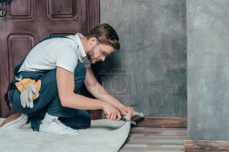 professional foreman cutting carpet while improving home