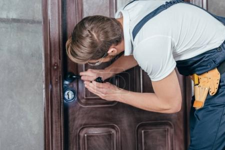 young manual worker in overall and goggles checking door lock with flashlight