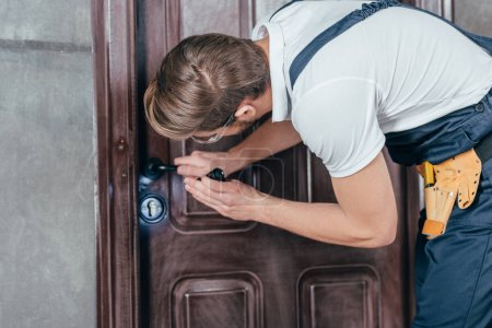 Photo for Young manual worker in overall and goggles checking door lock with flashlight - Royalty Free Image