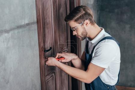 Photo for Young worker repairing door lock with screwdriver - Royalty Free Image