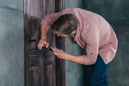 Photo for Young man repairing wooden door with flashlight and measuring tape - Royalty Free Image