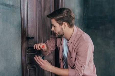 young man repairing door lock with screwdriver and flashlight