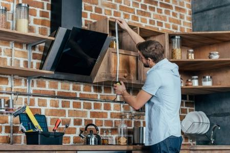 young man in eyeglasses measuring kitchen hood with tape