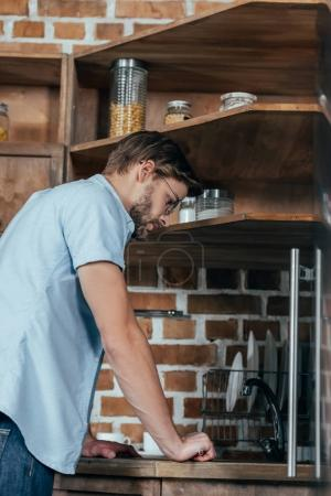 side view of casual young man repairing sink in kitchen