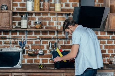 young man looking in toolbox with tools while working in kitchen