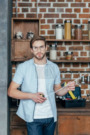 handsome young man in eyeglasses holding measuring tape and looking at camera