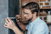 young man in eyeglasses measuring wall with tape at home